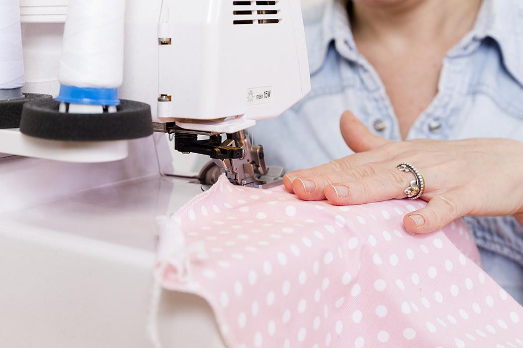 Dettaglio mani da donna alle prese con la macchina da cucire
